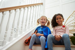 Two Girls Playing Dressing Up Games Sitting On Stairs stock photo