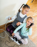 Two girls playing with electricity. Two small girls playing with electricity and wall outlers and smiling at home royalty free stock image