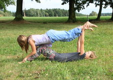 Two girls playing and exercising yoga on meadow Stock Photography