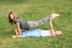 Two girls playing and exercising yoga on meadow. Two little girls - barefoot kids exercising yoga - supported exercises one above another by holding feet on Royalty Free Stock Images