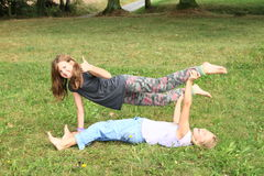 Two girls playing and exercising yoga on meadow Stock Photo