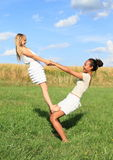 Two girls playing and exercising yoga on meadow Royalty Free Stock Photo