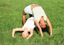 Two girls playing and exercising yoga on meadow. Two smiling girls - caucatian kid and tropical women exercising yoga - upward bow or wheel pose one over another Stock Images