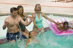 Two girls (7-9) playing with family in swimming pool. Royalty Free Stock Photography