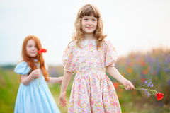Two girls playing with flowers in a summer field. Selected focus Royalty Free Stock Image