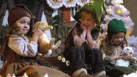 Two girls are playing with fluffy rabbits and the boy with a smile looks at them, waiting for Christmas, slow motion. Three children in old-fashioned clothes are stock video