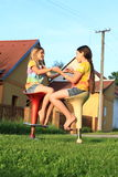 Two girls playing game while sitting on bar chairs stock image