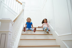 Two Girls Playing Game On Staircase At Home Royalty Free Stock Image