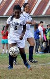 Two girls playing a girls` high school soccer game royalty free stock image