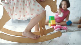 Two girls playing at home. Two cute girls playing with cubes and riding horse at home stock video footage