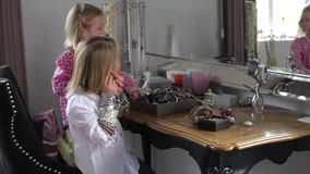 Two Girls Playing With Jewelry In Parents Bedroom. Girls standing at dressing table trying on mother's jewelry and earrings.Shot on Canon 5d Mk2 with a frame stock video footage