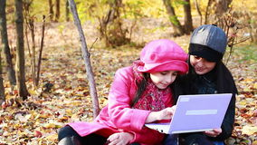 Two girls playing on laptop. Sisters have a fun time on laptop. Autumn stock footage