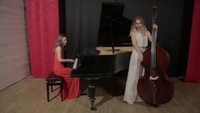 Two girls playing musical instruments. Piano and doublebass. Two girls play on musical instruments. Piano and contrabass stock video footage