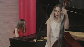 Two girls playing musical instruments. Piano and doublebass stock video