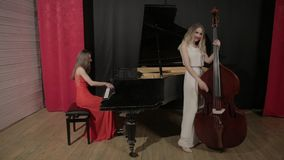 Two girls playing musical instruments. Piano and doublebass stock video footage