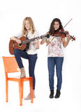 Two girls playing musical instruments Royalty Free Stock Photos