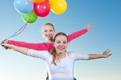 Two girls playing outside with balloons Stock Photos
