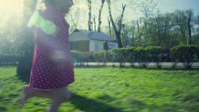 Two girls playing in the park. Two girls and a dog playing in the park at spring day stock video footage