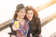 Two girls playing with a phone Stock Photos