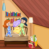 Two girls playing pillow in bedroom Stock Photo