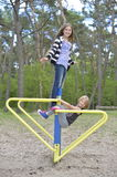 Two girls are playing on the playground on the yellow metal attraction. It's windy. Royalty Free Stock Images