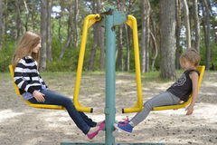 Two girls are playing on the playground on the yellow metal attraction. It's windy. Royalty Free Stock Photo