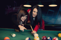 Two girls playing pool game Stock Image
