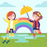 Two girls playing in the rain and rainbow Stock Photos