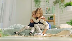 Two girls playing in the room on the bed and hug.  stock video footage