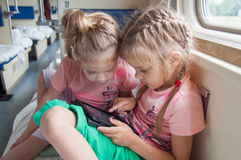 Two girls playing in the second-class tablet in a train. Two girls play with enthusiasm in the electronic tablet sitting on the bed in a second-class train Royalty Free Stock Images
