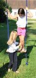 Two girls playing on swing Royalty Free Stock Image