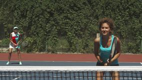 Two girls playing tennis in the pair. Girls took a position one after another on the court. They are focused and confident of victory stock video