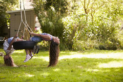 Two Girls Playing Together On Tire Swing In Garden Royalty Free Stock Image
