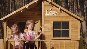 Two girls are playing in a treehouse. Two adorable little girls are playing in a treehouse in the summer stock video