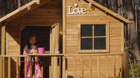 Two girls are playing in a treehouse. Two adorable little girls are playing in a treehouse in the summer stock footage