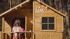 Two girls are playing in a treehouse. Two adorable little girls are playing in a treehouse in the summer stock video footage