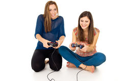 Two girls are playing video games. Two happy girls play video games Royalty Free Stock Photos