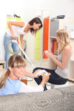Two girls playing video games. While their roommate is cleaning the house Royalty Free Stock Photos