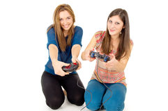 Two girls are playing video games isolated. On white background Royalty Free Stock Image