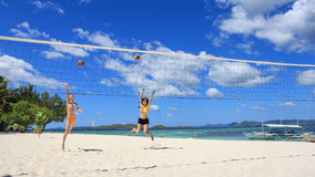 Two girls playing volleyball on white beach. Two young girls jump and play volleyball using coconuts on white beach, with background of beautiful blue sky and Stock Photo