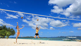 Two girls playing volleyball on white beach. Two young girls jump and play volleyball using coconuts on white beach, with background of beautiful blue sky and Royalty Free Stock Images