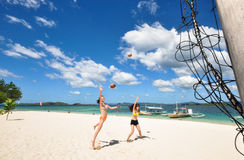 Two girls playing volleyball on white beach. Two young girls jump and play volleyball using coconuts on white beach, with background of beautiful blue sky and Royalty Free Stock Image