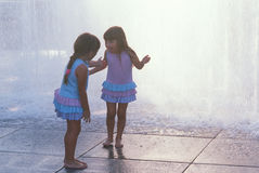 Two girls playing in a water fountain Stock Photo