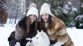 Two girls playing with white husky dog in snow . Slow motion.  stock footage
