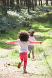 Two Girls Playing In Woods Together Stock Photo