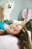 Two girls playingwith a Pomeranian on the bed close-up. vertical Royalty Free Stock Photos