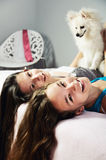 Two girls with a Pomeranian lay on the bed and laughing close-up Stock Photos