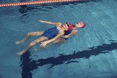 Two Girls in a Pool Water Rescue Training. Preteen Swimming Help Safe Stock Photography