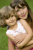 Two girls portrait. Beautiful sisters summer portrait on the grass Stock Images