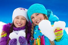 Two girls portrait holding snow hearts Stock Photography